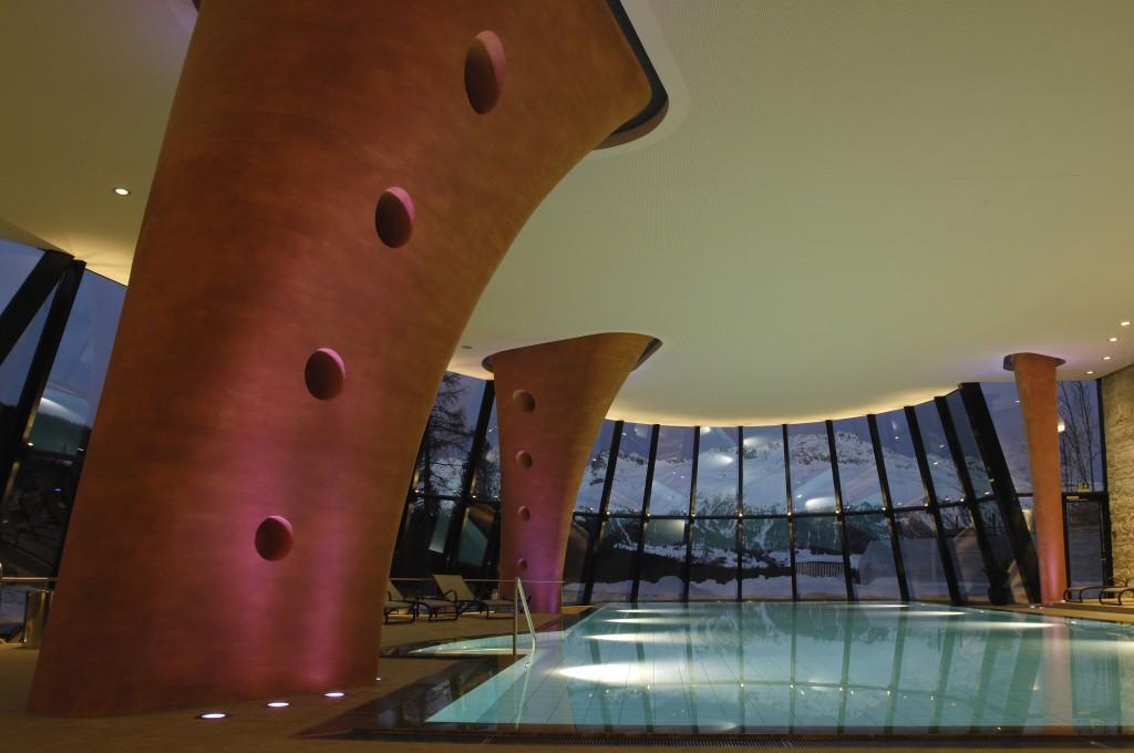 Der Indoor-Pool des Grand Hotel Kronenhof mit Blick in die nächtliche Berglandschaft rund um Pontresina.