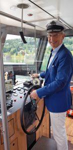 """Der Hotelchef ist auch Kapitän: Hubert Koller am Steuerrad der """"MS KOLLERs Swan"""". Foto: Bauroth"""
