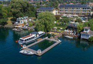 Das KOLLERs hat direkten Seezugang. Ein Hit ist der ganzjährig beheizte Pool im See. Links ist das Luxus-Bootshaus zu sehen, rechts das Seebad mit Sauna und gemütlichen Ruheoasen. Foto: KOLLERS Hotel