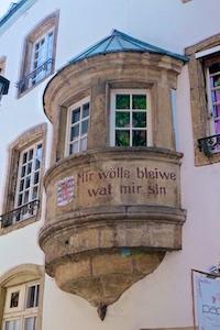 """""""Mir wölle bleiwe wat mir sinn"""" (""""Wir wollen bleiben, was wir sind""""). Anlass für diesen Wahlspruch war die Luxemburgkrise 1867, der von Napoléon III. beabsichtigte, aber nicht realisierte Erwerb des Großherzogtums, das Teil des Deutschen Bundes und dessen Staatsoberhaupt Wilhelm III. der Niederlande war."""